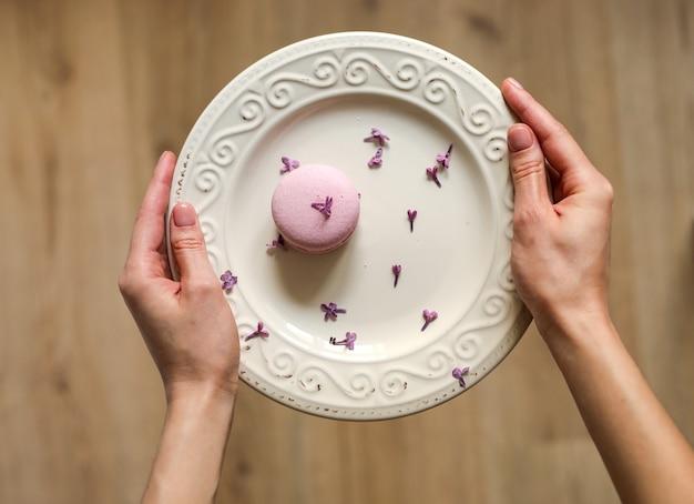 Przycięty widok kobiety trzymającej talerz z różowym pysznym francuskim makaronikiem lub makaronikiem z kwiatami bzu na drewnianym tle.