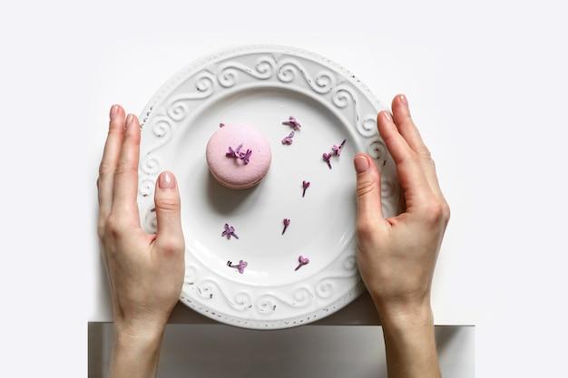 Przycięty widok kobiety trzymającej talerz z różowym pysznym makaronikiem francuskim lub makaronikiem z kwiatami bzu na białym tle.