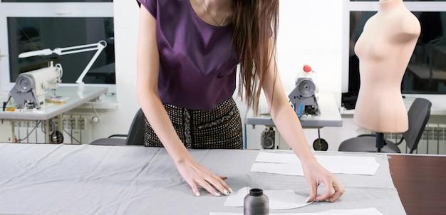 Przycięty widok krawca w pracy, rysowanie linii na tkaninie kredą w pracowni atelier
