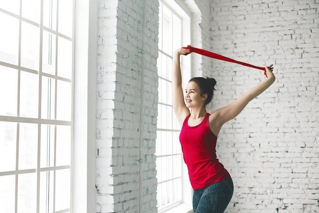 Przycięty widok pięknej, szczęśliwej młodej kobiety o elastycznym atletycznym ciele, wykonującej ćwiczenia rozciągające w pomieszczeniu, pomagając sobie czerwonym paskiem fitness, uśmiechając się, gdy cieszy się tak zdrową aktywnością