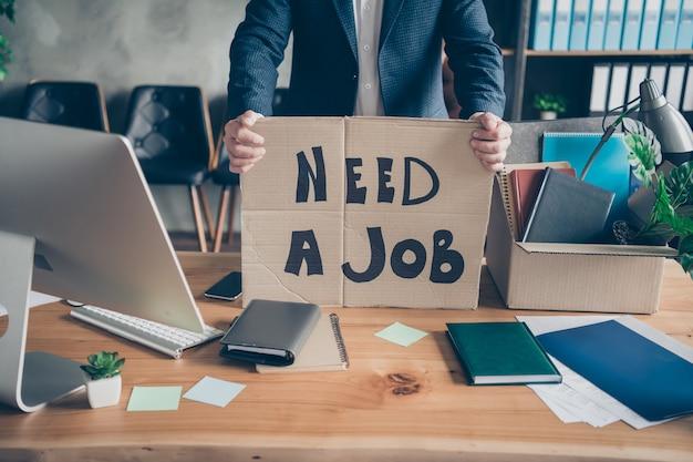 Przycięty widok portret jego zwolnił bezrobotnego nieszczęśliwy mężczyzna agent broker wykonawczy specjalista trzymający w rękach papierowy afisz mówiący potrzebuję pracy na nowoczesnym poddaszu przemysłowym miejscu pracy stacja w pomieszczeniu