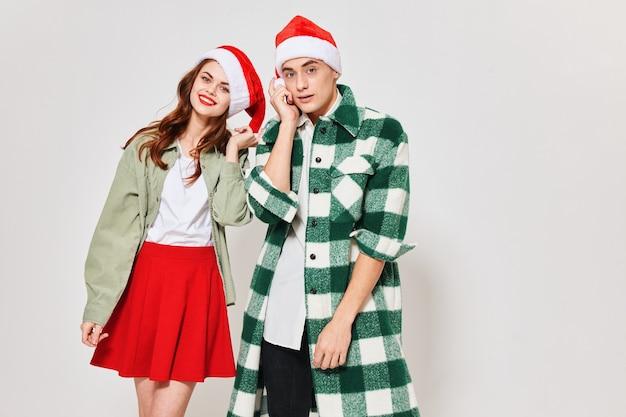 Przycięty widok szczęśliwej kobiety i przystojnego mężczyzny w świątecznym kapeluszu na jasnym tle. wysokiej jakości zdjęcie