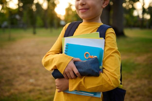 Przycięty widok uroczego uśmiechniętego chłopca w wieku szkolnym z przyborami szkolnymi i skoroszytami w rękach pozowanie do kamery w parku miejskim o zachodzie słońca