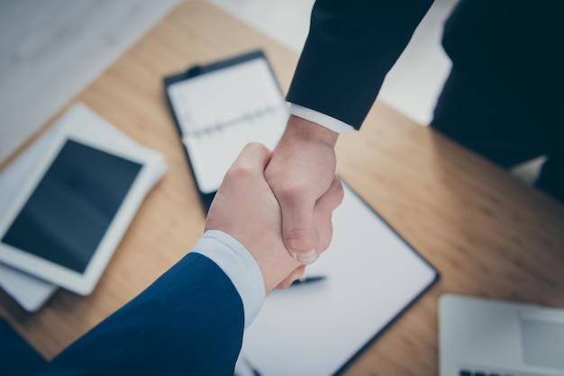 Przycięty widok z bliska dwóch stylowych eleganckich mężczyzn ekonomista prawnik bankier finansista uścisk dłoni spotkanie spotkanie umowa zrobione ubezpieczenie uzgodnienie nad drewnianym stołem biurko miejsce pracy stacja robocza