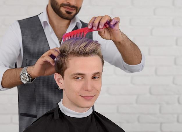 Przycięty widok z boku fryzjera wykonującego tonację fioletowo-włosową dla młodego chłopca.