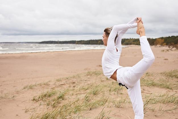 Przycięty widok z boku sportowego młodzieńca ćwiczącego na świeżym powietrzu, trenującego balankę i elastyczność, wykonującego zgięcie w tył, stojącego w natarjasanie na piasku. męski jogin utrzymujący równowagę, wykonujący pozę króla tancerza