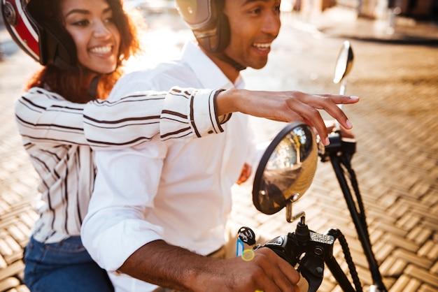 Przycięty widok z boku zadowolonej pary afrykańskiej jeździ na nowoczesnym motocyklu na ulicy