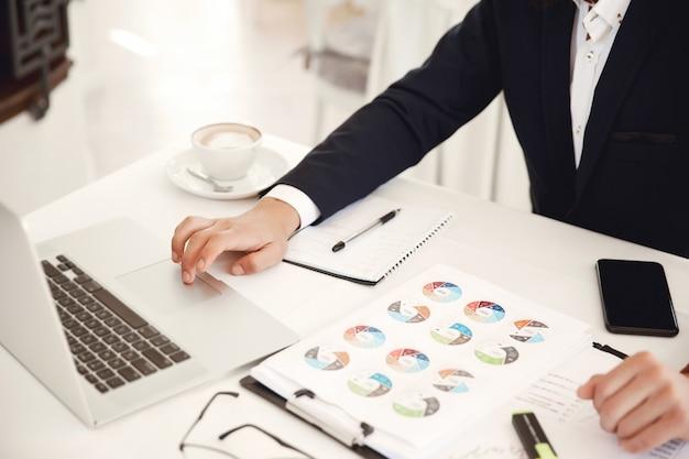 Przycięty widok z przodu miejsca pracy biznesmena w restauracji z laptopem, telefonem komórkowym, diagramami i latte