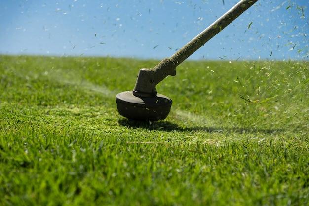 Przycinaj ogrodnika trawą w ogrodzie za pomocą trymera do chwastów