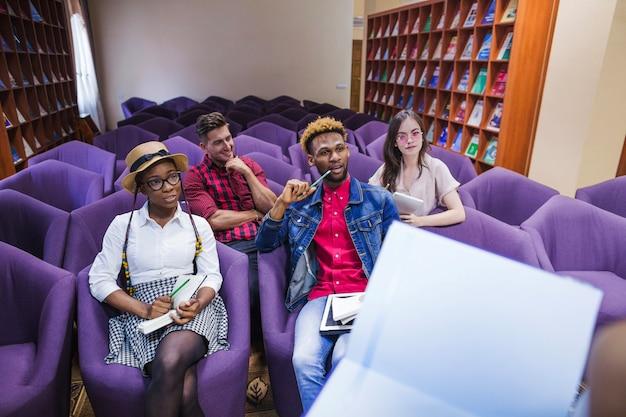 Przycinaj studenta z notebookiem i kolegami z klasy