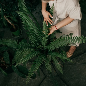 Przycinaj zdjęcia kobiecych dłoni, dbając o kwiaty w przydomowym ogrodzie. prywatność w małym zakątku zieleni. pojęcie kwiaciarstwa
