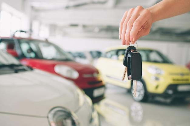 Przycinający zbliżenie dealer samochodowy trzyma out kluczyki do kamery