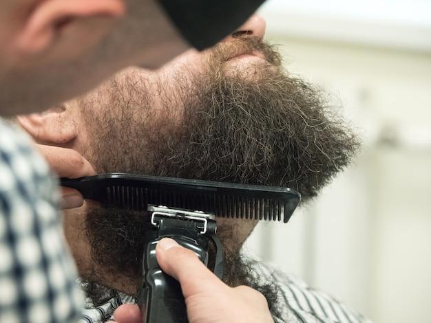 Przycinanie brody maszynkami do strzyżenia w sklepie fryzjerskim. ścieśniać.