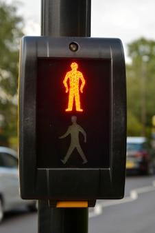 Przycisk czekać na sygnał sygnalizacji świetlnej z jasnym stopem podświetlonym na przejściu dla pieszych