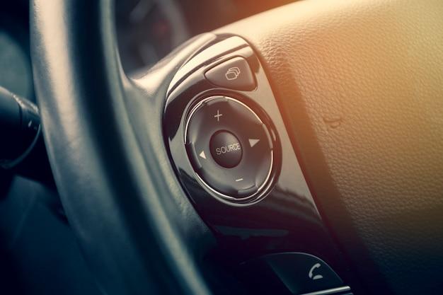 Przycisk multimedialny na kierownicy wielofunkcyjnej w luksusowym samochodzie.