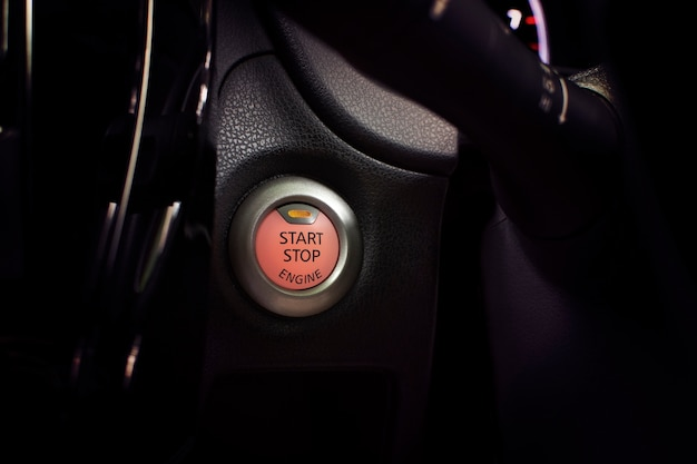 Przycisk uruchamiania silnika samochodu z pomarańczowym światłem.