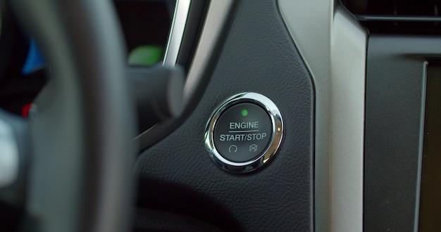 Przycisk zapłonu samochodu jest naciskany, aby uruchomić i zatrzymać pojazd. naciśnięcie przycisku zasilania zapłonu, aby uruchomić silnik samochodu hybrydowego z zapłonem bezkluczykowym.