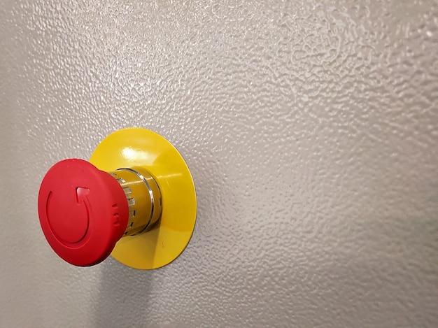 Przycisk zatrzymania awaryjnego, ochrona przed katastrofami. koncepcja przemysłowa. czerwony przycisk na stole w ciemnym tle niski klucz.