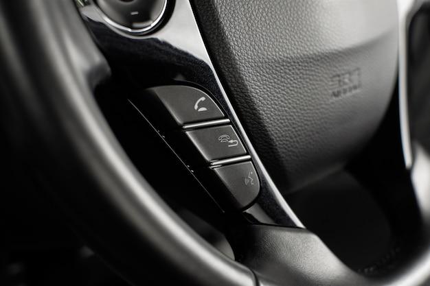Przyciski sterowania telefonem w panelu sterowania multimediami na kierownicy w luksusowym samochodzie.