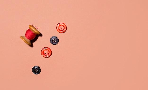 Przyciski w kolorze czerwonym na brązowej przestrzeni. skopiuj miejsce. koncepcja szycia i naprawiania starych rzeczy. minimalizm