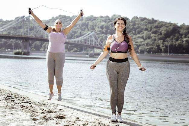 Przydatna aktywność. zachwycone pozytywne kobiety korzystające ze skakanki podczas skoków na plaży