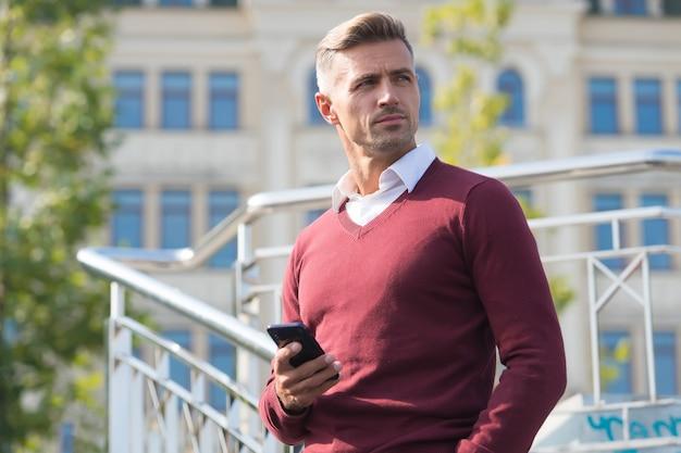 Przydatna aplikacja. komunikacja biznesowa. komunikacja przez internet. nowoczesna komunikacja. biznesmen posiada telefon komórkowy. przystojny mężczyzna z telefonem na zewnątrz. mobilny styl życia. połączenie internetowe.