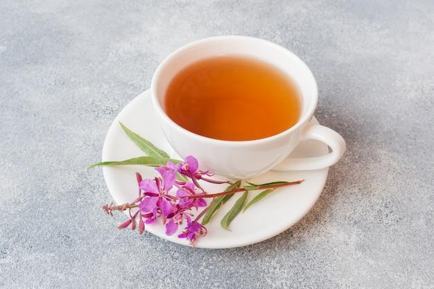 Przydatna herbata ziołowa z sfermentowanych liści chwastów na szarym tle. tradycyjna rosyjska koporye herbata ivan chai kopii przestrzeń.