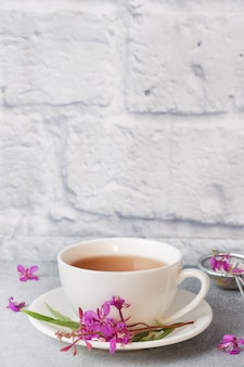 Przydatna herbata ziołowa z sfermentowanych liści chwastów na szarym tle.