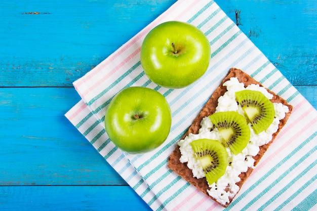 Przydatna przekąska, szybki zdrowy posiłek. zbożowy chleb z domowej roboty twarogu i kiwi plasterkami na błękitnym drewnianym tle. dwa soczyste zielone jabłka na serwetkach.