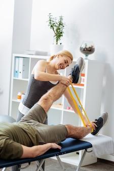 Przydatna rzecz. ładna, pozytywna kobieta używająca gumki podczas pracy z pacjentem