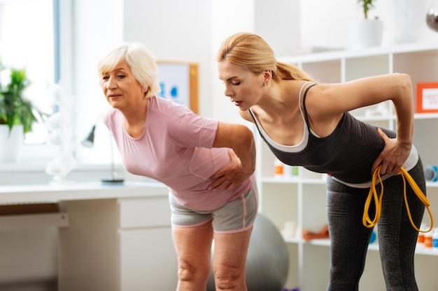 Przydatne ćwiczenie. ładna, ładna kobieta rozmawiająca ze swoim pacjentem, pochylająca się do przodu podczas treningu