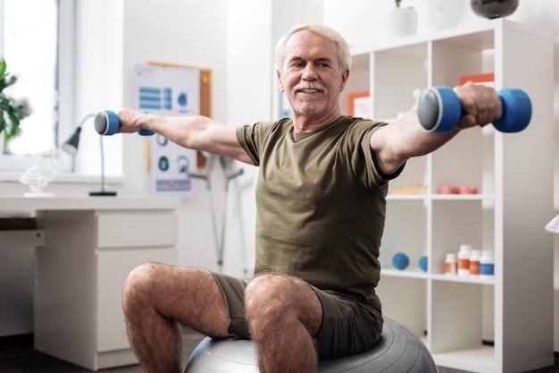 Przydatne ćwiczenie. radosny, aktywny mężczyzna w dobrym nastroju podczas ćwiczeń fizycznych while