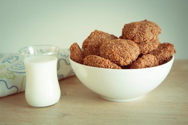 Przydatne domowe ciasteczka i szklanka mleka na stole.