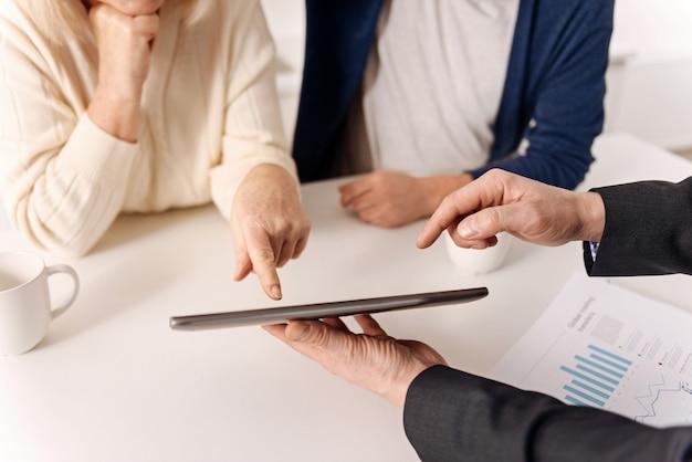 Przydatne nowoczesne gadżety w naszych rękach. doświadczony, dojrzały i wykwalifikowany agent nieruchomości pracujący z kilkoma starszymi klientami przy jednoczesnej trosce i korzystaniu z tabletu