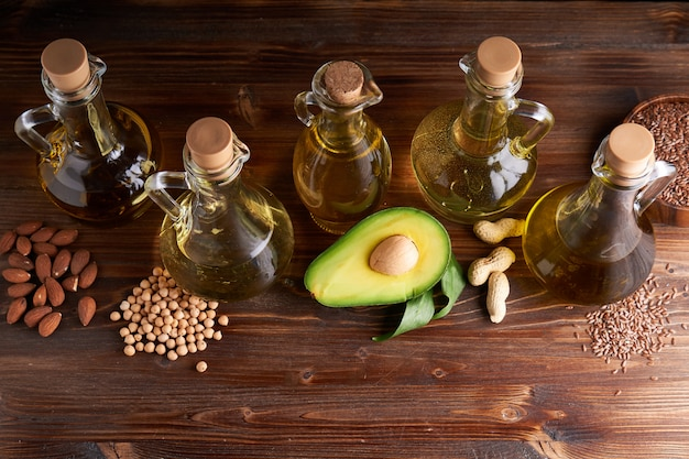 Przydatne oleje roślinne w szklanych butelkach. olej z awokado, olej z ciecierzycy, olej lniany, olej arachidowy, olej migdałowy.