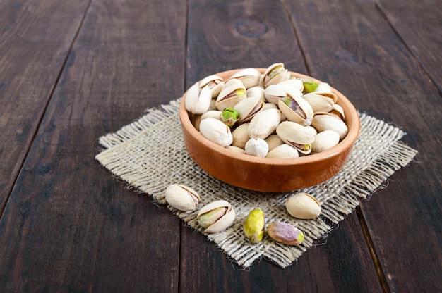 Przydatne orzechy - pistacje w ceramicznej misce na ciemnym drewnie.