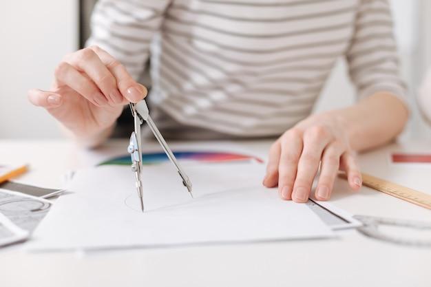 Przydatne umiejętności zbliżenie kompasów w rękach profesjonalnej kobiety wykonującej rysunek i siedzącej przy stole podczas pracy nad projektem
