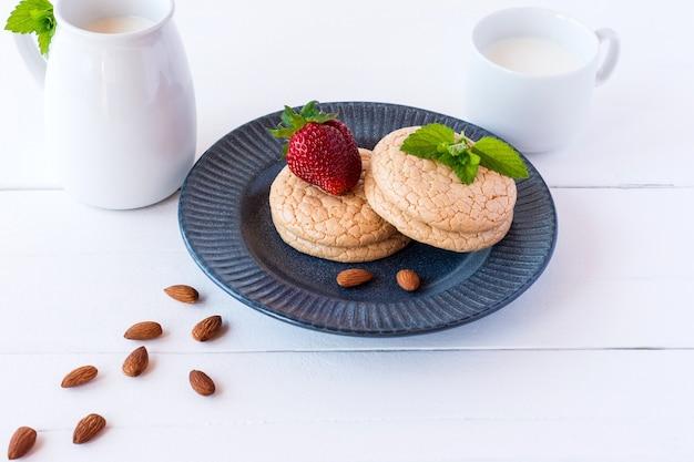 Przydatne wielkopostne ciasteczka z mąki migdałowej z truskawkami i mlekiem na białym drewnianym tle. selektywne skupienie.
