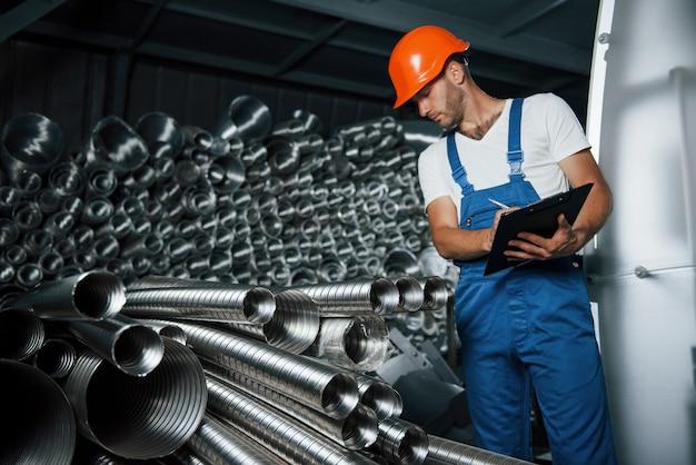 Przygląda się bliżej. mężczyzna w mundurze pracuje nad produkcją. nowoczesna technologia przemysłowa.