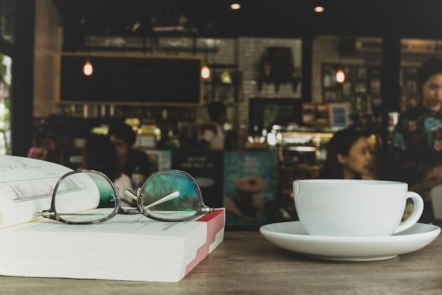 Przygląda się szkła na książce z filiżanką kawy na drewnianym biurku w plamie.