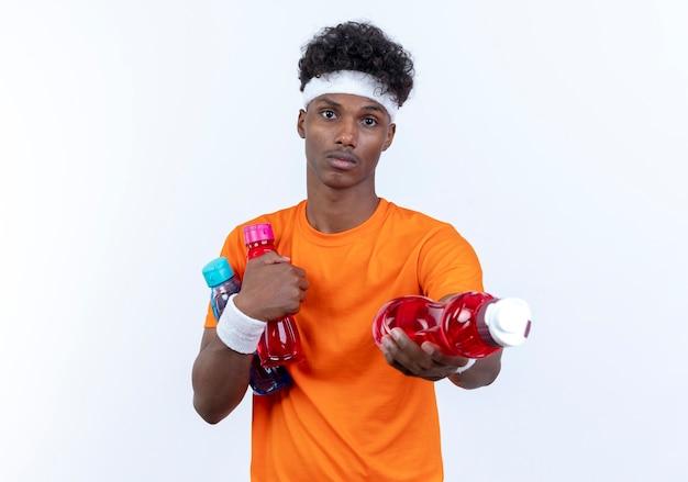Przyglądający się młody afro-amerykanin wysportowany mężczyzna noszący opaskę na głowę i nadgarstek trzymający butelkę wody do aparatu