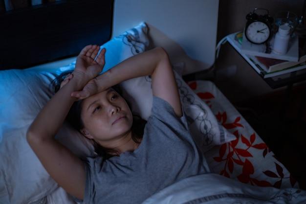 Przygnębiona azjatka nie może spać na łóżku.zespół bezsenności bezsenności po nieszczęśliwym i niepokojącym jej trybem życia.dorosły odczuwa smutek.złe emocje.