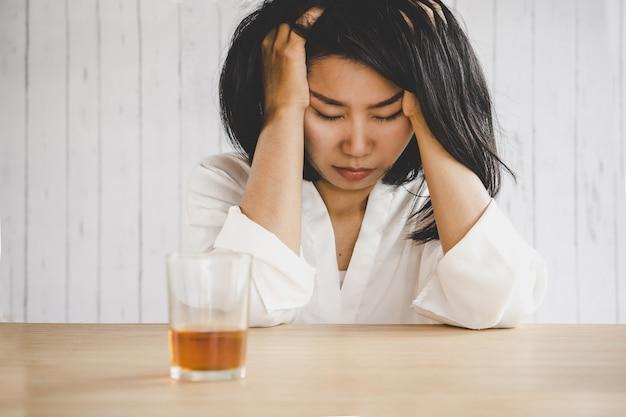 Przygnębiona azjatycka kobieta z pić szkło alkohol