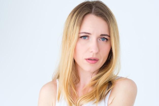 Przygnębiona blondynka na białej ścianie.