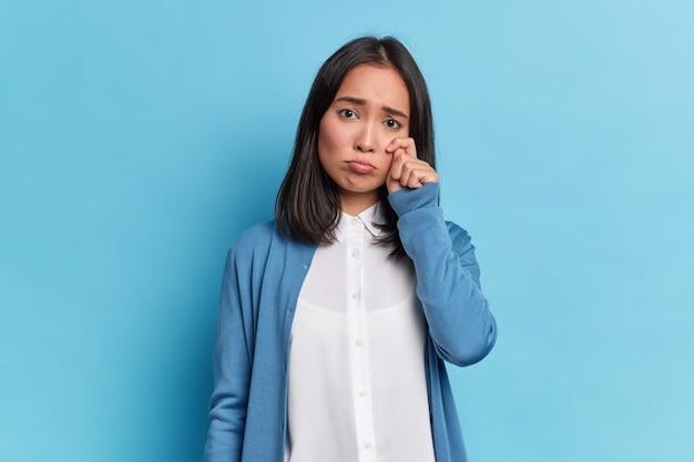 Przygnębiona brunetka ociera łzy, płacze z rozpaczy, niezadowolony smutny wyraz twarzy nosi schludne ubrania, stawia czoła nierozwiązywalnym problemom życiowym