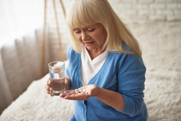 Przygnębiona chora kobieta biorąc środki przeciwbólowe.