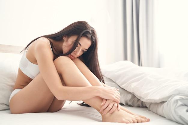 Przygnębiona długowłosa kaukaska dama w bieliźnie siedzi samotnie z ramionami owiniętymi wokół kolan