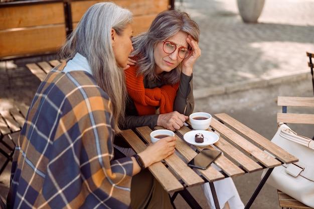Przygnębiona dojrzała dama w okularach i staranny przyjaciel si w ulicznej kawiarni w jesienny dzień