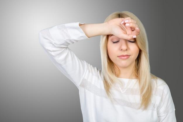 Przygnębiona dojrzała kobieta dotyka czoło i utrzymuje oczy zamykających