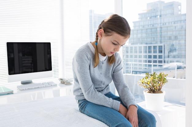 Przygnębiona dziewczyna siedzi na stole egzaminacyjnym